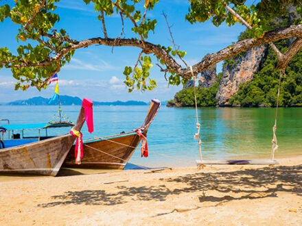 Traditional longtail boats moored on beach in Thailand